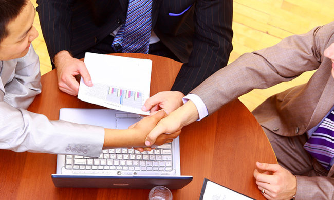 business handshake over workplace